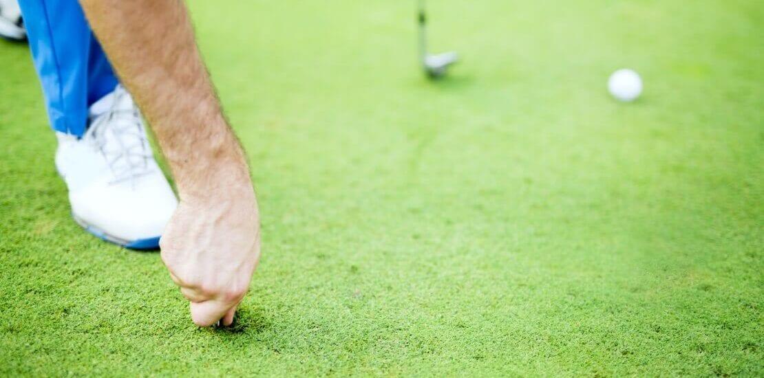 Golfspieler repariert Loch im Boden
