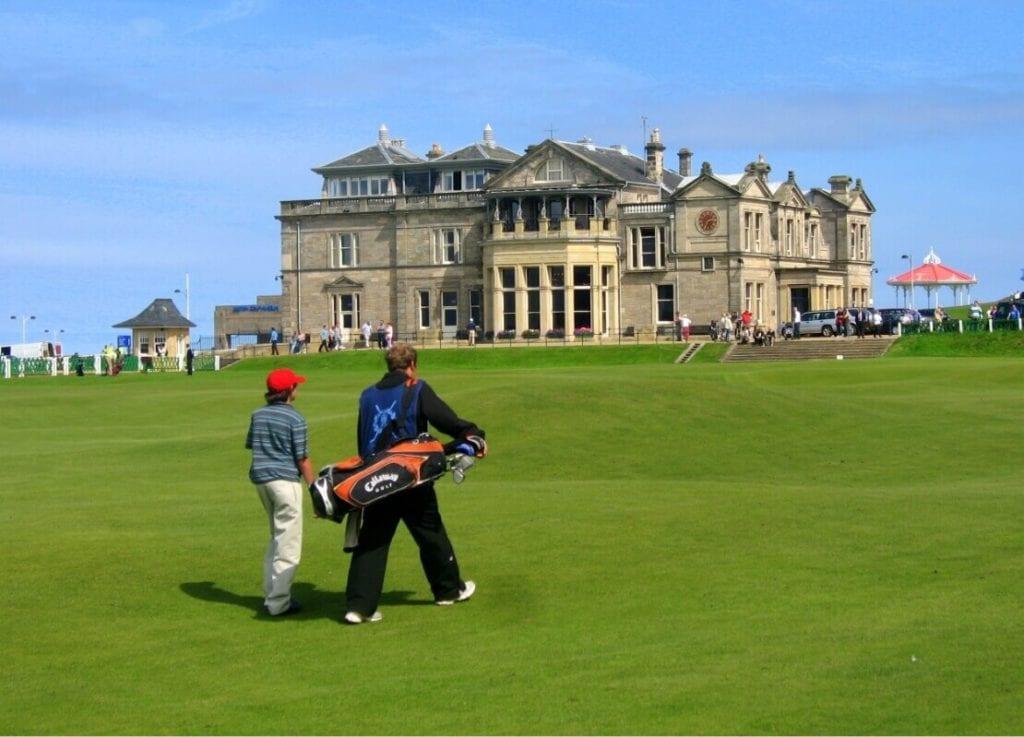 Ein Mann geht mit einem Teenager auf einem Golfplatz
