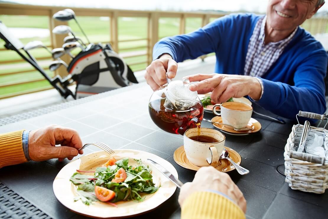 Golfer gießt seinem gegenübersitzendem Golfpartner bei einem gemeinsamen Essen eine Tasse Tee ein.