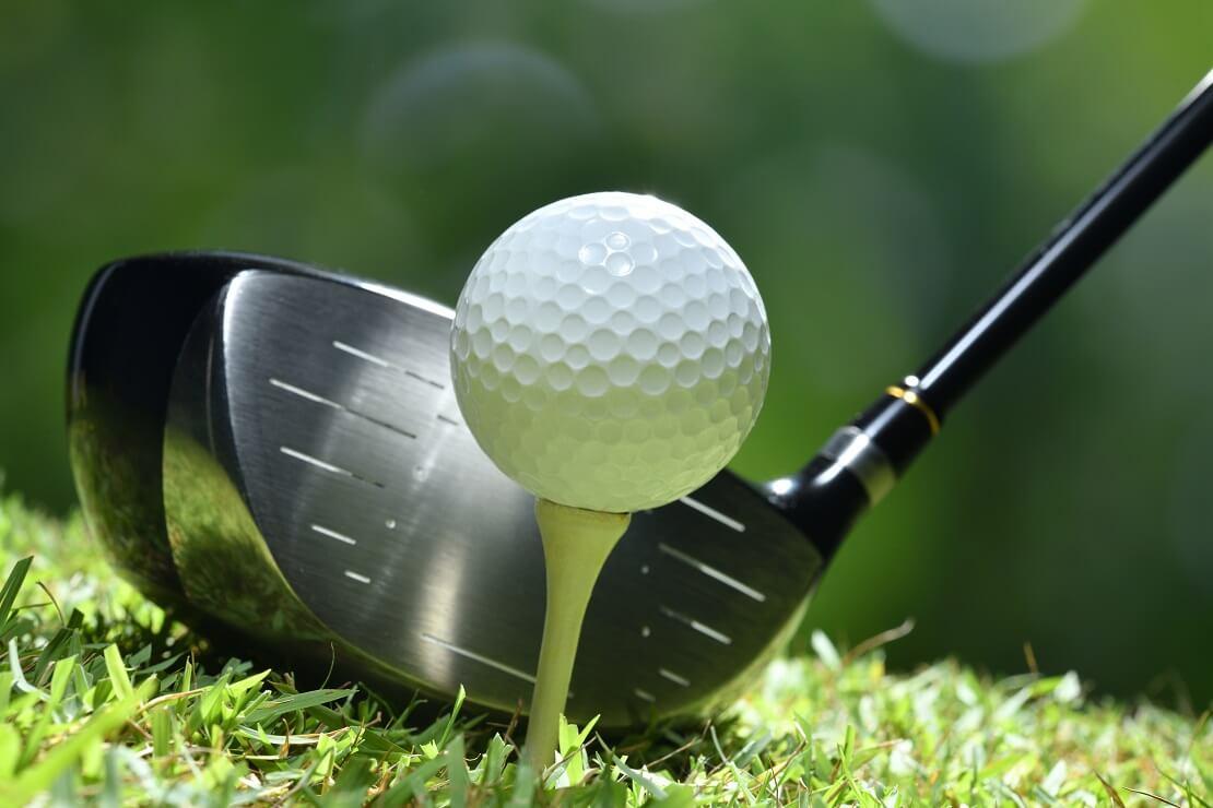 Golfball auf einem Tee dahinter das Schlägerblatt eines Drivers