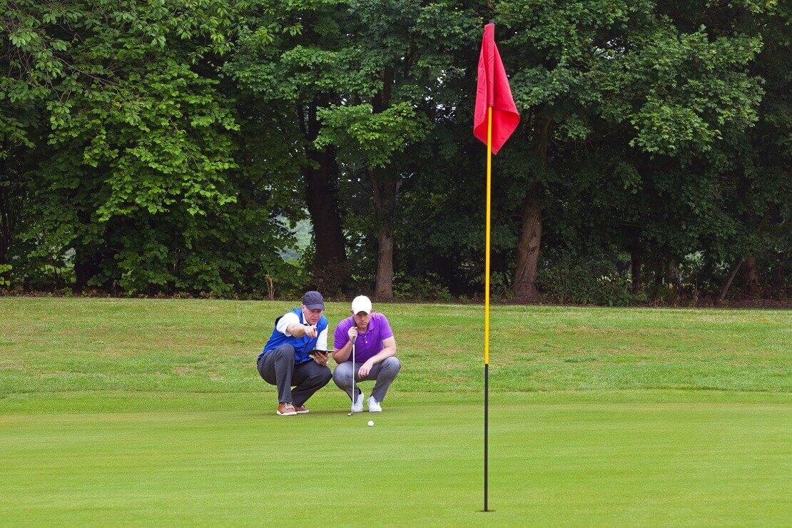 Fahne im Vordergrund, Spieler und Caddy lesen das Grün im Hintergrund