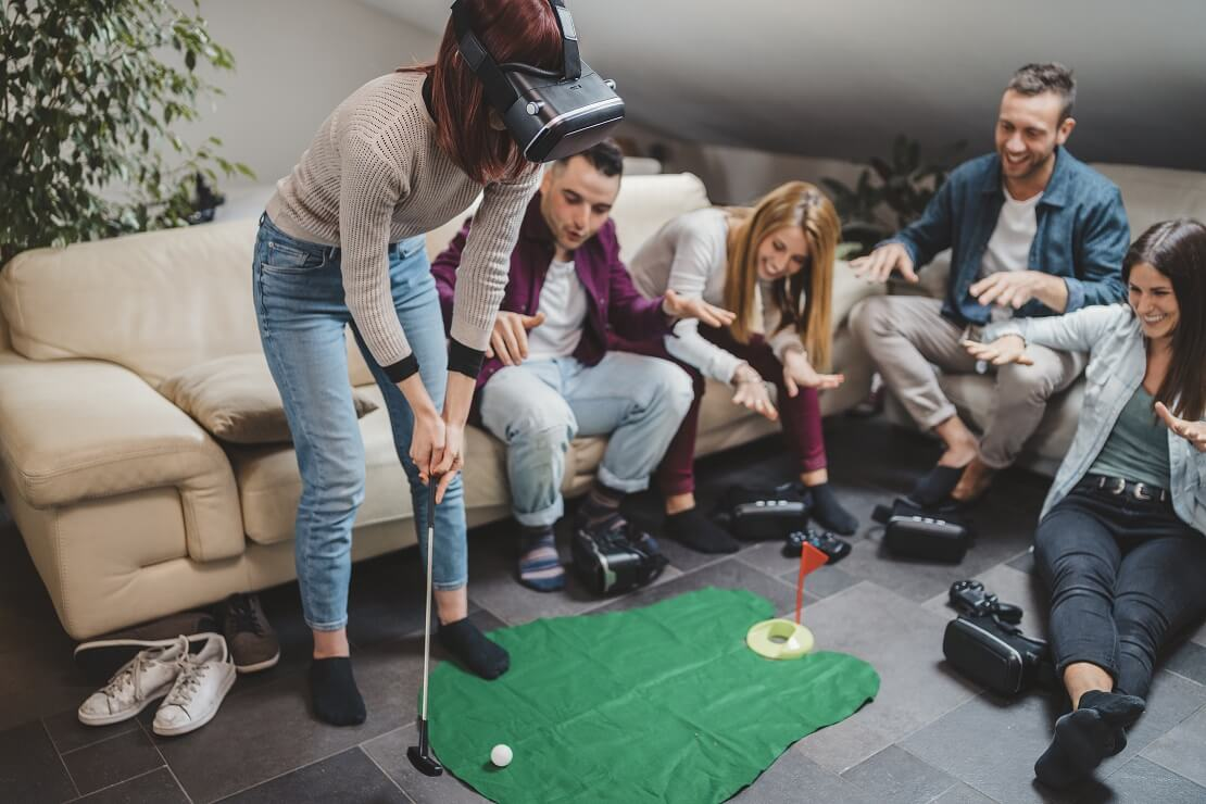 Frau steht mit einer VR-Brille in der Mitte einer Gruppe und spielt VR-Golf