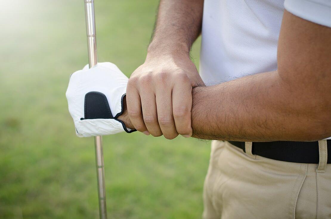 Golfer packt an sein Handgelenk in der anderen Hand trägt er einen Golfhandschuh und hält einen Golfschläger
