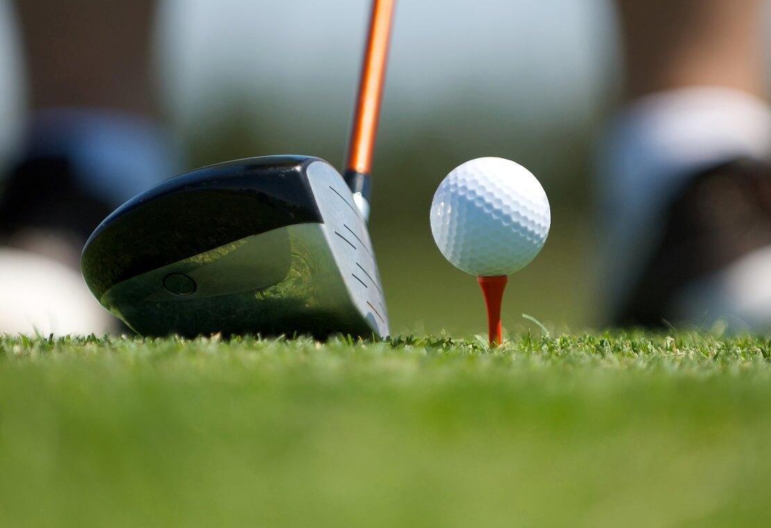 Golfball legt auf dem Tee hinter dem Ball ist ein Golfschläger angesetzt