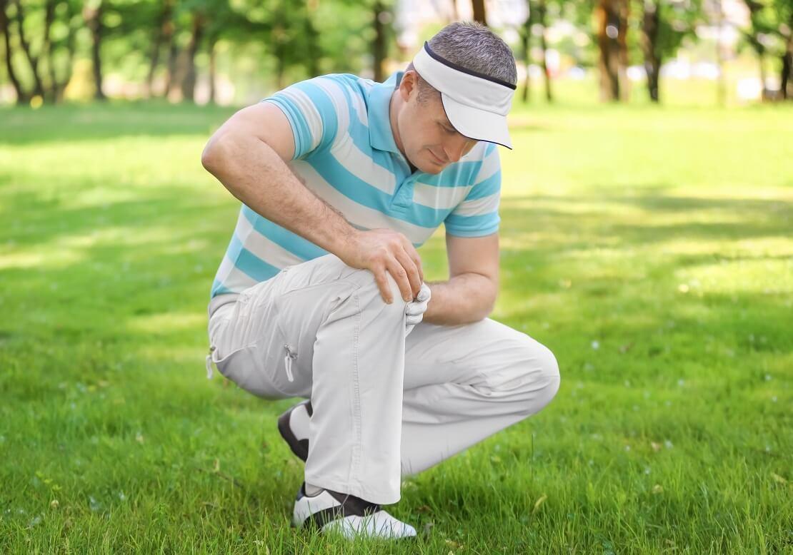 Golfer hält sich schmerzverzerrt das Knie