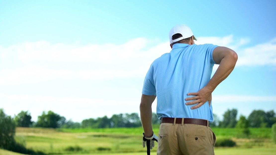 Golfer hält sich schmerzhaft den Rücken