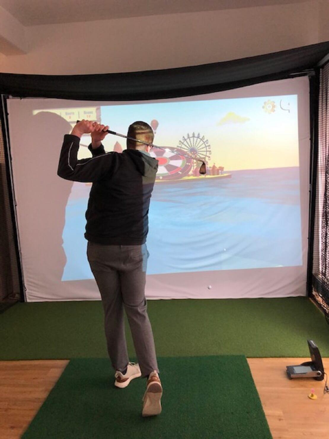Golfer vor einem Golfsimulator spielt den Ball auf eine Dartscheibe