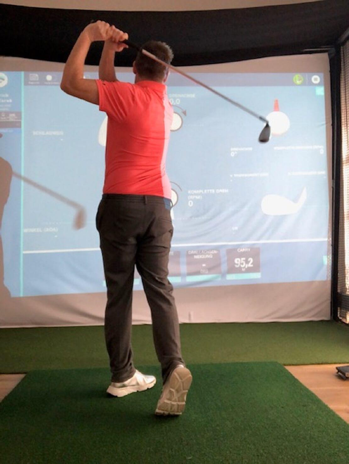 Golfer spielt mit einem Golfsimulator
