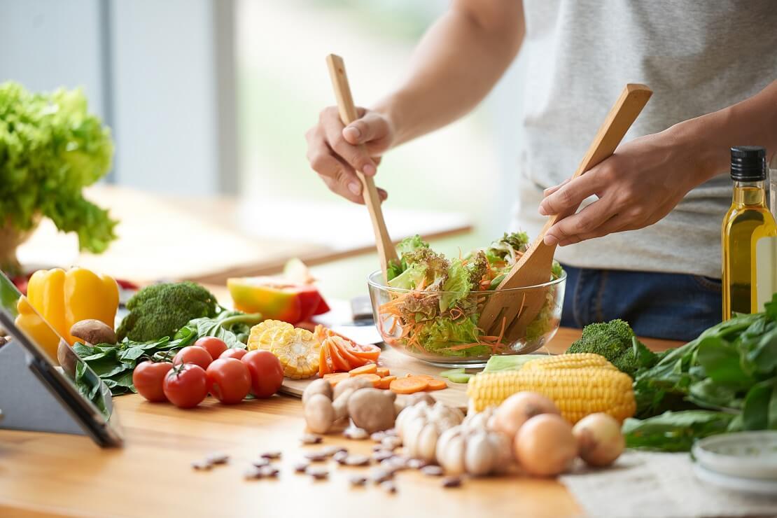 Mann bereitet Salat aus Gemüse vor, auf dem Tisch liegt weiteres Gemüse
