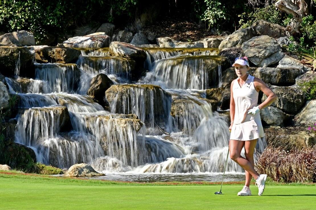Lexi Thompson steht im Golfdress vor einem Wasserfall