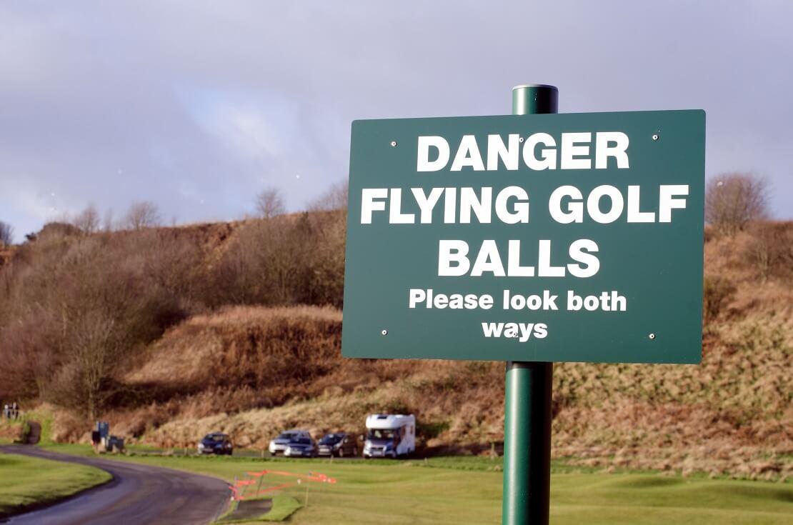"""""""Danger Flying Golf Balls"""" auf einem Schild"""