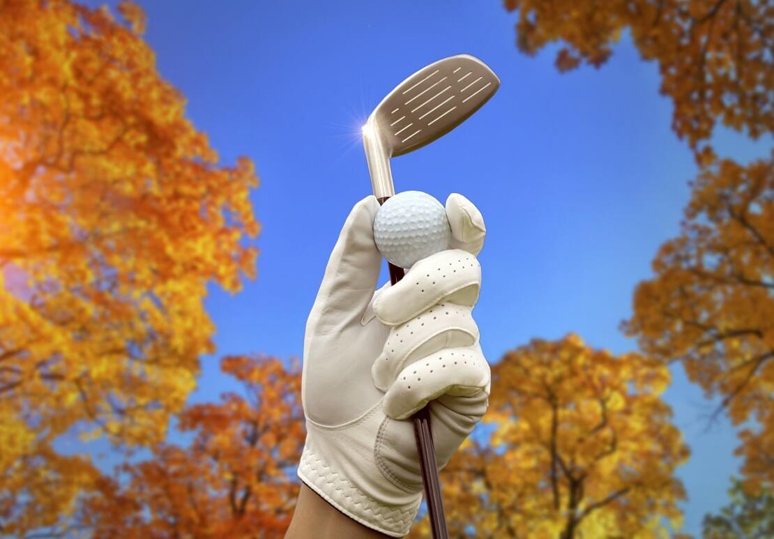 Golfschläger wird in die Luft gereckt mit herbstlichen Bäumen und blauem Himmel im Hintergrund